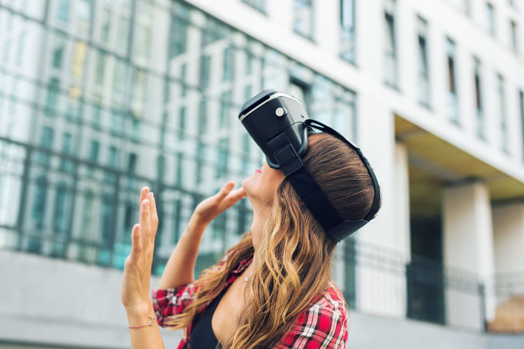Woman standing outdoors wearing virtual reality headset