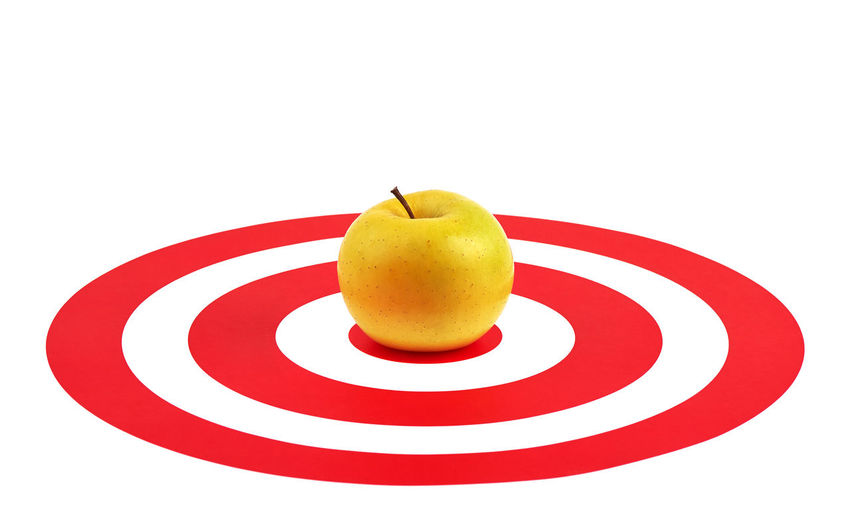 Close-up of apple on plate against white background