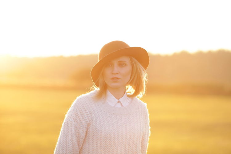 Close-up of young woman standing on grass field during sunset