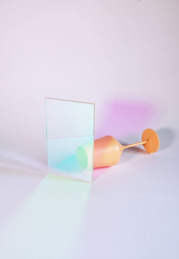 Close-up of multi colored glass on table against white background