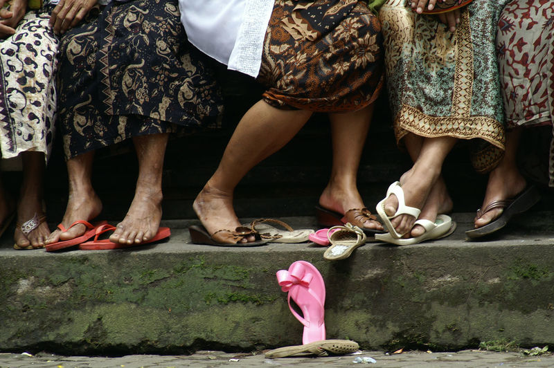 Low section of women standing by sandal