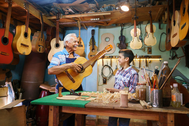 Senior man playing guitar while standing with boy in workshop