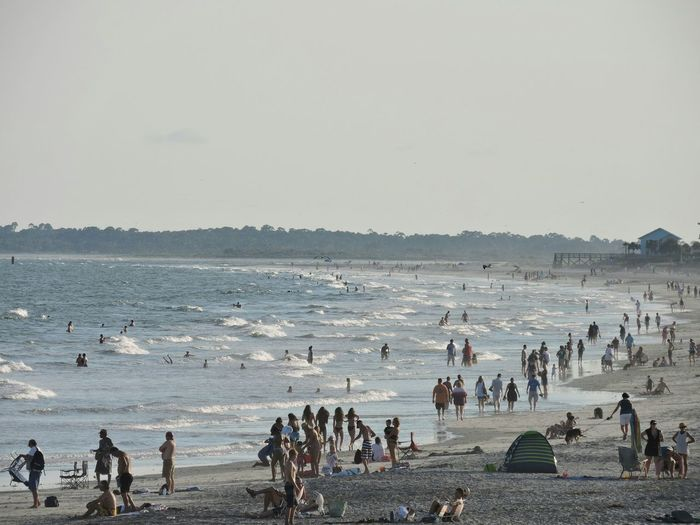 People enjoying at beach during sunny day