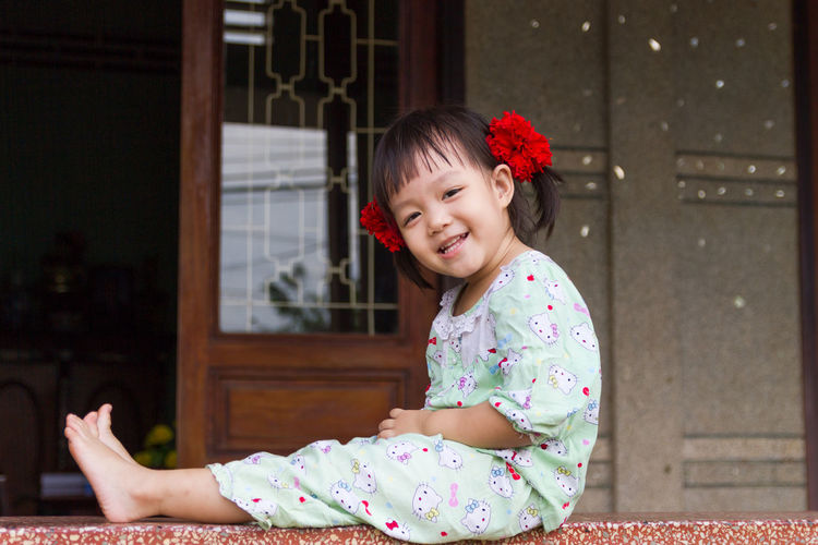 Cute girl wearing red flowers while sitting on retaining wall