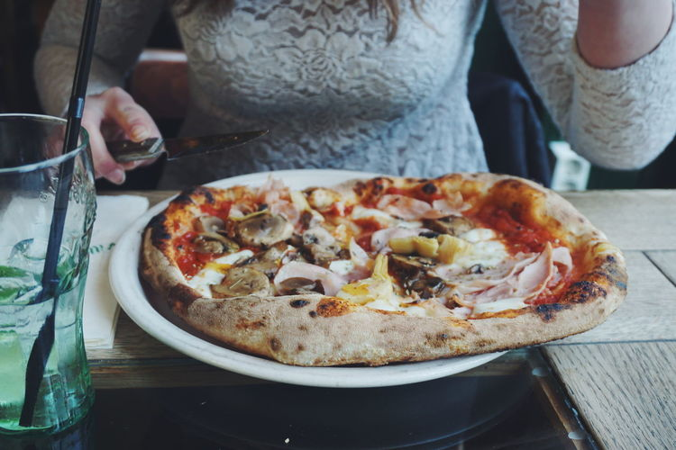 Midsection of woman eating pizza at restaurant