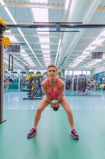 Full Length Of Woman Doing Exercise With Kettlebell At Gym