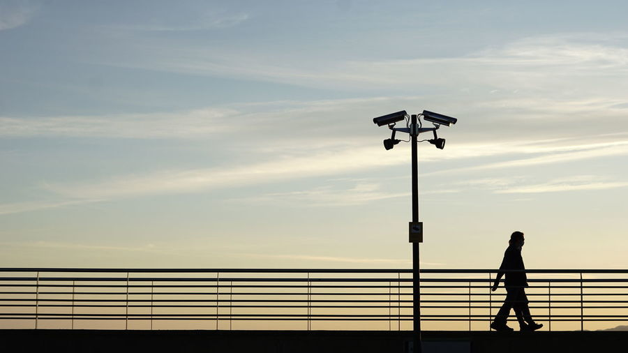 Silhouette man standing by railing against sky