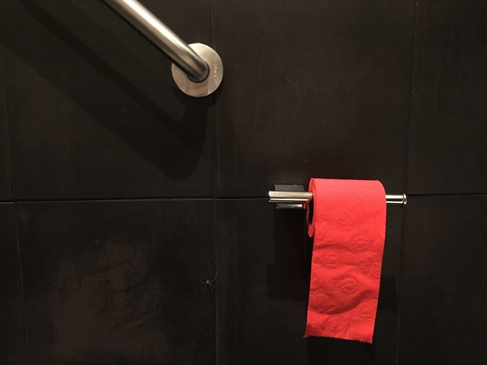 Close-up of red toilet paper on wall in bathroom