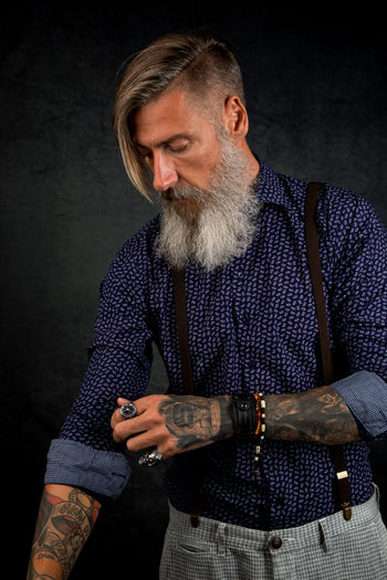 Portrait in vintage look of a cool and bearded hipster Beard Standing Mature Adult One Person Indoors  Three Quarter Length Clothing Men Males  Front View Studio Shot Looking Gray Waist Up Black Background Hipster - Person Tattoo Suspenders Vintage Casual Clothing Model Posing Lifestyles Isolated Stylish