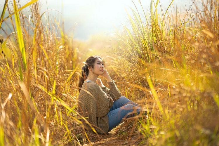 Side view of young woman sitting on field