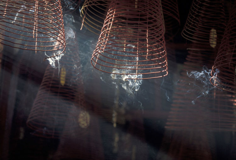 Low angle view of burning spiral incenses hanging at temple