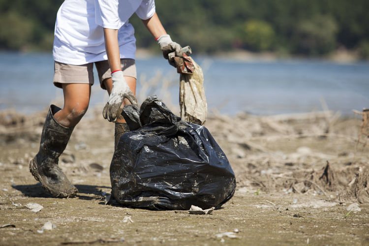 Volunteer cleaning dirty beach Activist  Cleaning Collecting Nature Volunteer Volunteering Beach Clean Coast Ecology Ecology Problem Environment Garbage Garbage Bag Holding Outdoors Picking Pollution Unrecognizable Person Volunteer Work Waste