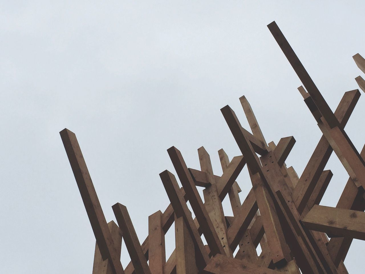 Low Angle View Of Wooden Logs Against Clear Sky