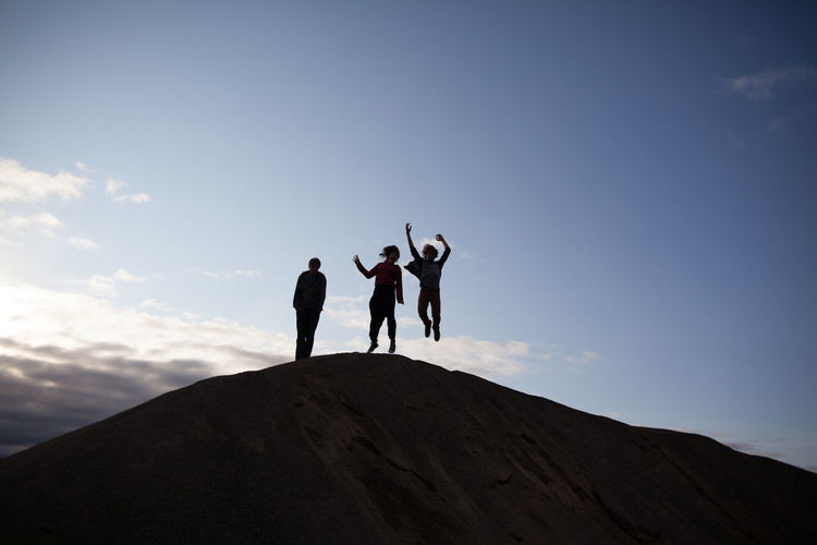 Low angle view of people enjoying on mountain top against blue sky
