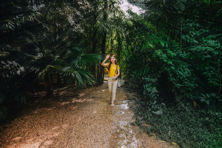 Woman walking amidst plants in forest