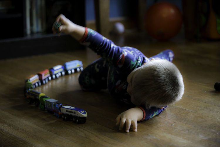 Baby Babyhood barefoot Child Childhood Flooring Focus On Foreground Full Length Hardwood Floor Indoors  Innocence Lying Down One Person Playing Real People Toddler  Toy Wood Young