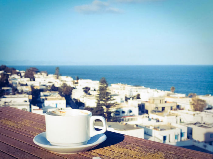 Coffee cup by sea against sky
