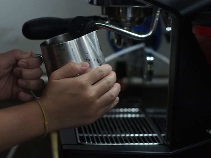 Cropped Hands Of Barista Making Coffee In Cafe
