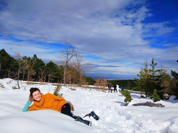 Cheerful woman lying on snowy field against sky
