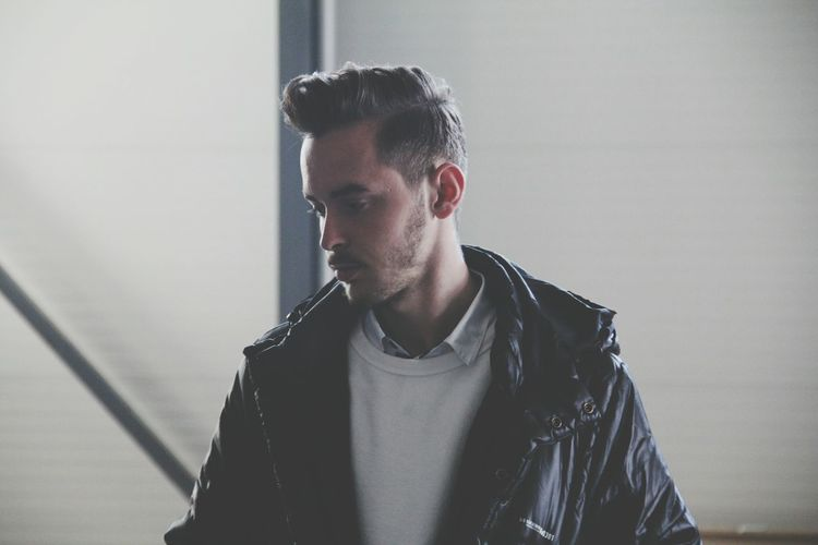 Close-up of handsome man wearing leather jacket against wall