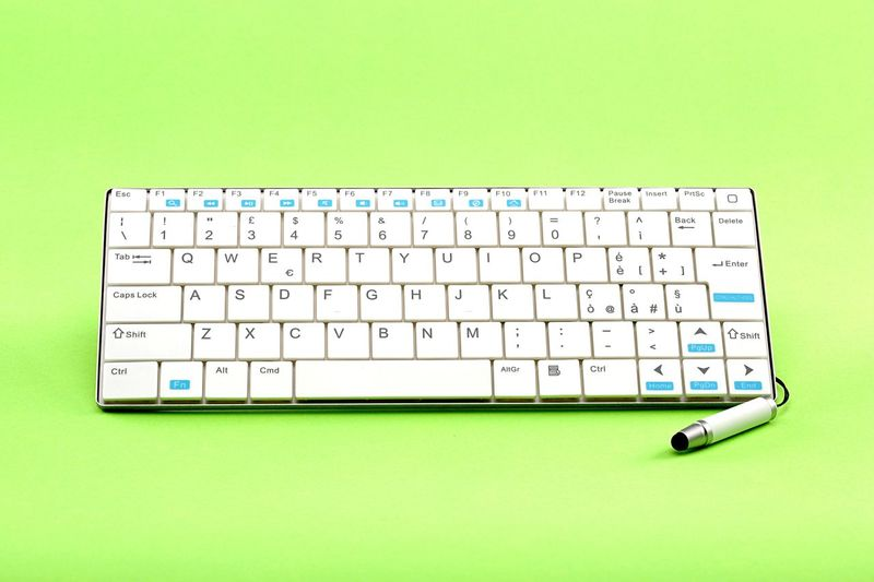 High Angle View Of Computer Keyboard On Green Table