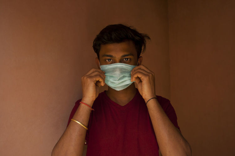 Portrait of young man with mask against wall