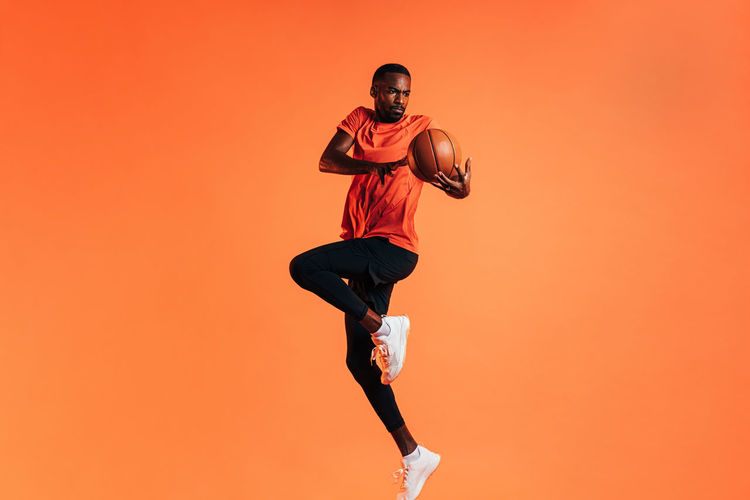 Man with basketball jumping against orange background