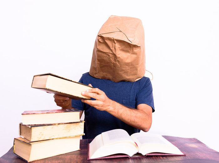 Side view of man reading book on table against white background