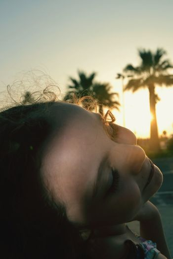 Close-up of smiling girl against sky during sunset