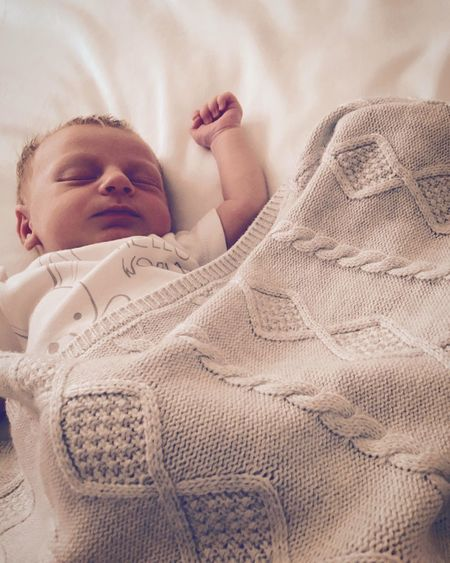 Blond baby sleeping on bed