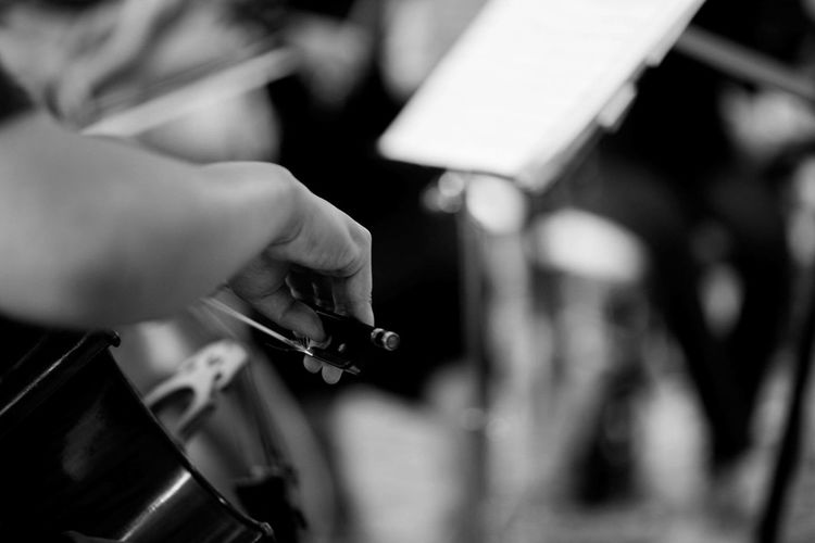 Close-up of person playing cello in orchestra