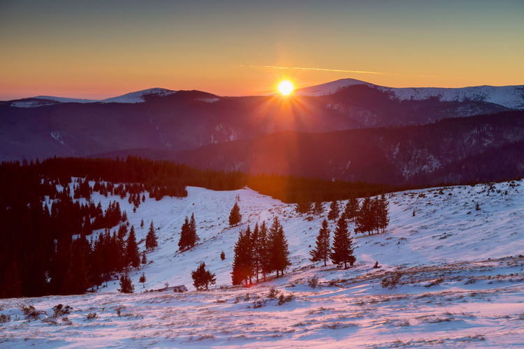 Scenic view of mountains against sky during winter at sunset