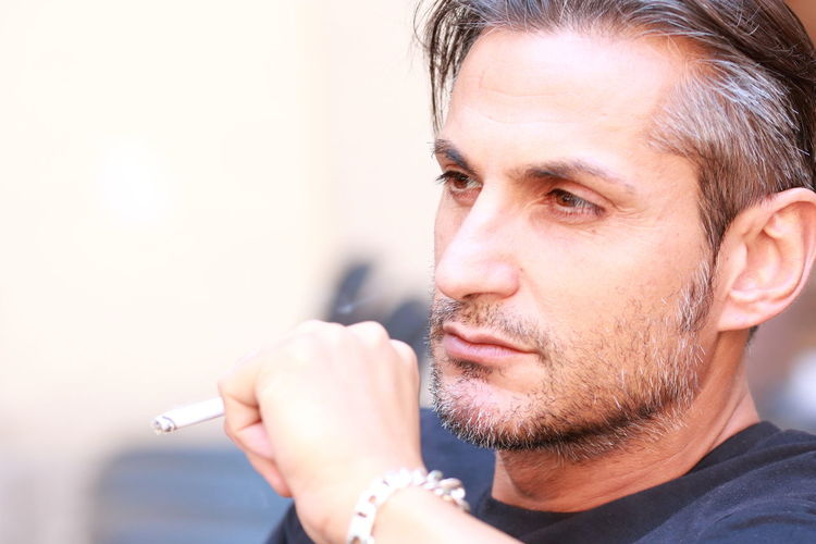 Close-Up Of Man Looking Away While Smoking Cigarette
