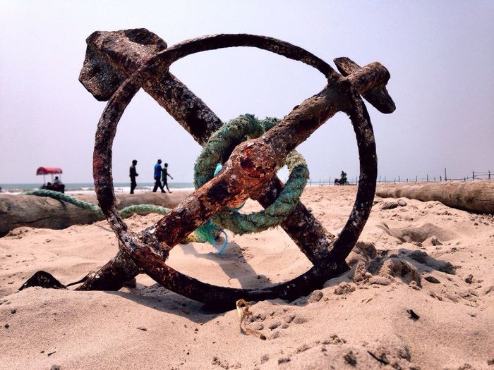 Rusty anchor on beach against clear sky