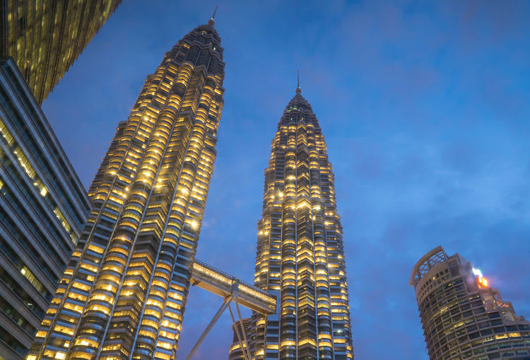 Low angle view of illuminated petronas towers against blue sky at dusk