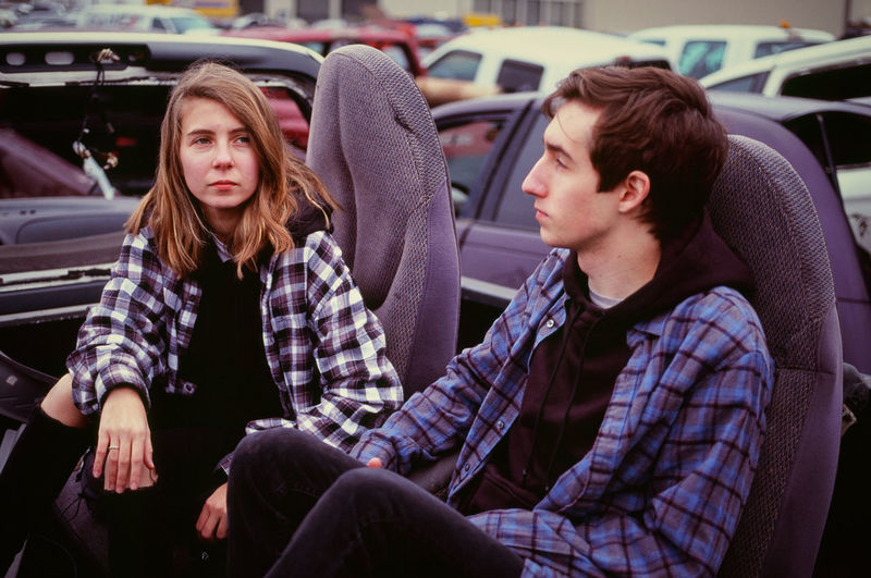 Young couple sitting in remains of a car in an auto salvage yard