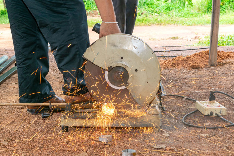 Low Section Of Man Cutting Metal With Circular Saw At Construction Site
