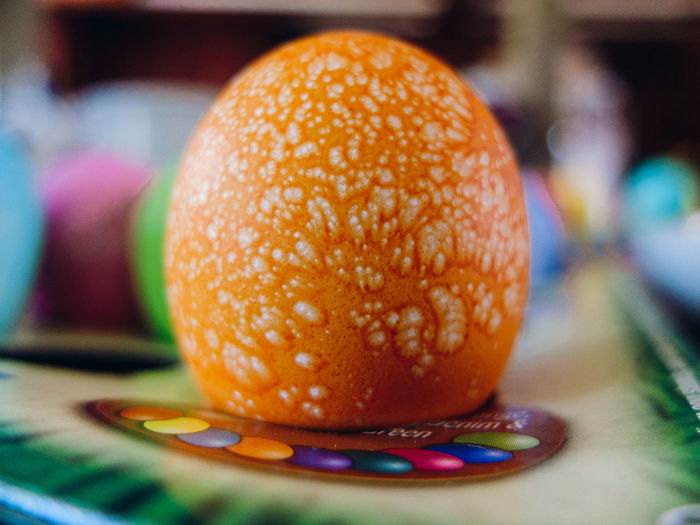 Close-Up Of Orange Dyed Easter Egg On Table