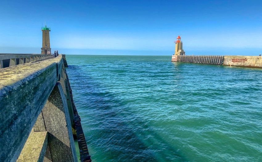 The piers and lighthouses of the harbor of Fécamp, France, forming a gate to the open sea Water Built Structure Architecture Tower Sea Sky Guidance Lighthouse Direction Building Exterior Building Nature Clear Sky Blue Day Security Travel Destinations Horizon Scenics - Nature Outdoors