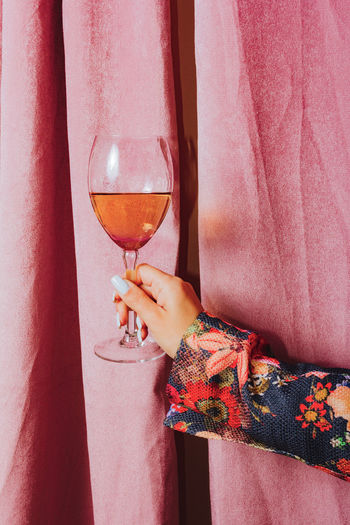 Midsection of woman holding wine glass