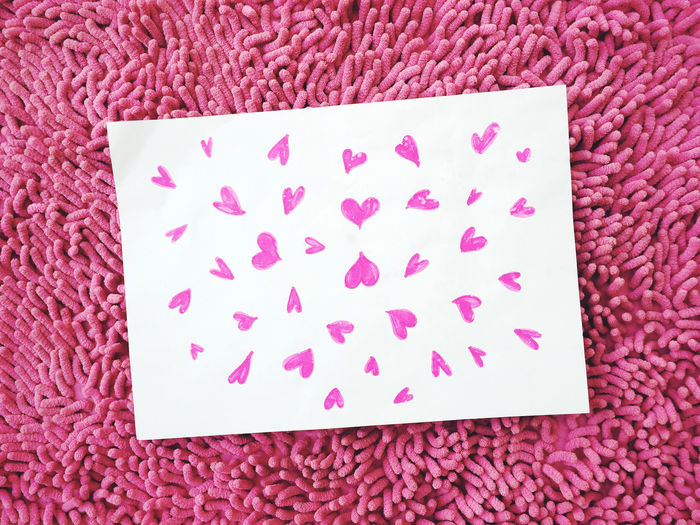 Close-Up Of Heart Shaped Drawn On Paper At Carpet