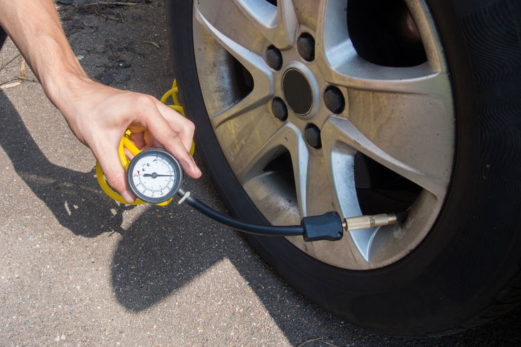 Cropped hands checking tire pressure