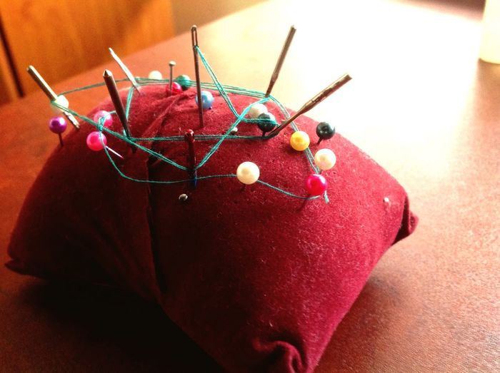 Close-Up Of Straight Pins In Pillow On Table