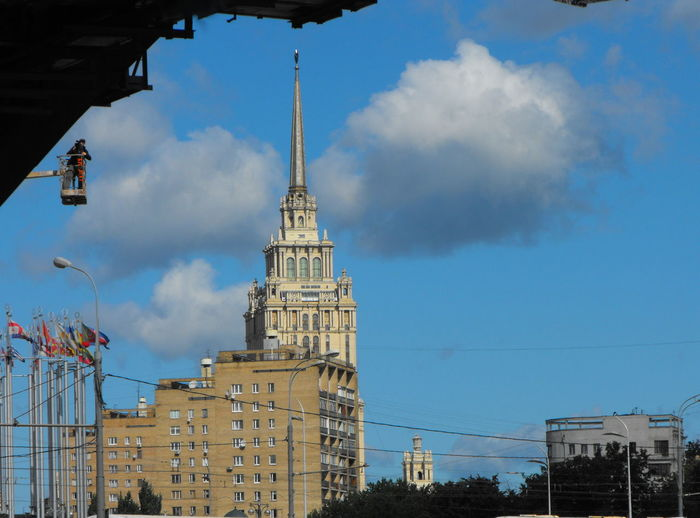 A Moscow scene City Life Moscow Repairing Worker Architecture Building Building Exterior Building Maintenance Built Structure City Cloud - Sky Day Flags History Low Angle View Nature Outdoors Repair Man Sky Skyscraper Soviet Architecture Spire  The Past Tower Travel Destinations