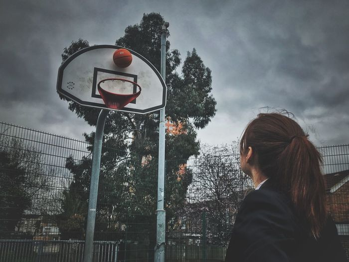 Low Angle View Of Woman Looking At Basketball Hoop Against Cloudy Sky