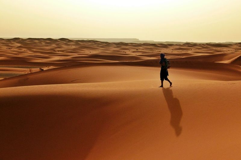 Full length of man walking on sand dunes at desert