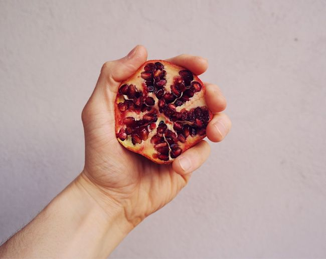 Cropped Hand Holding Pomegranate Against Wall