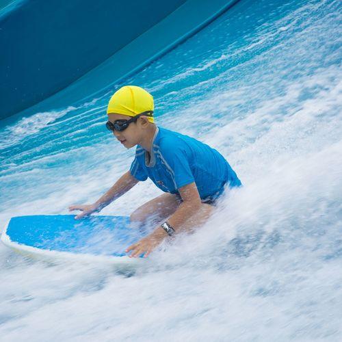 Boy surfing in sea