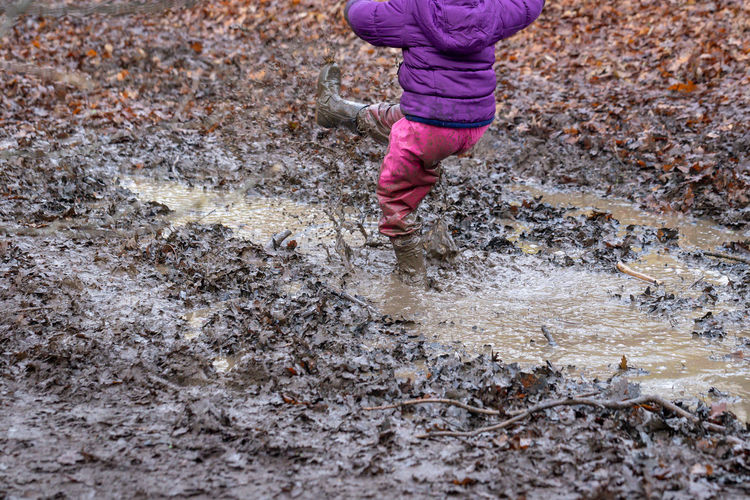 Low section of child playing in muddy puddle at land