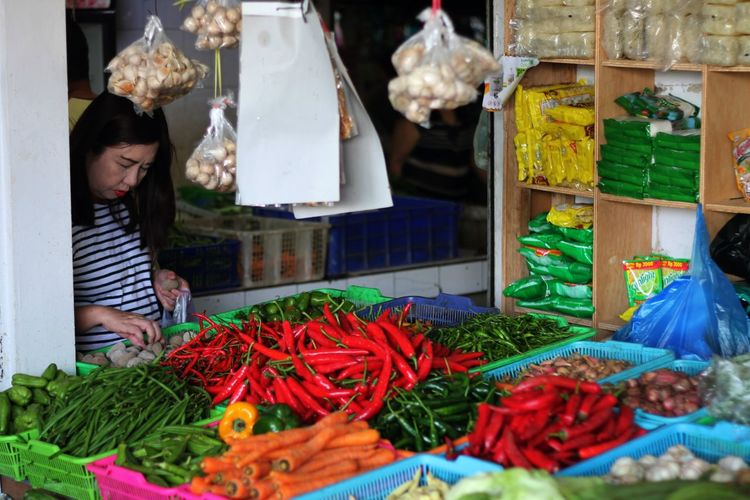 Woman picking vegetable while standing at market